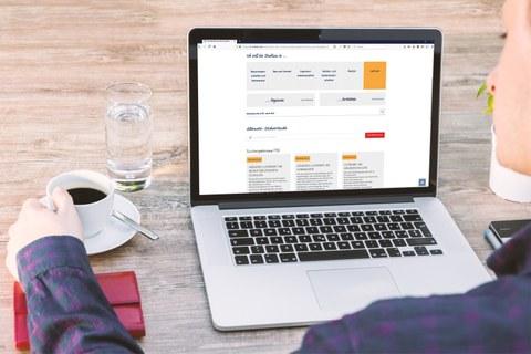 Das Foto zeigt eine Person, welche an einem Laptop sitzt, auf dessen Bildschirm die Webseite des Studieninformationssystems der TU Dresden geöffnet ist. Neben dem Laptop befinden sich ein Wasserglas und eine Kaffeetasse.