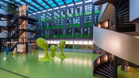 Das Foto zeigt das Foyer des Andreas-Pfitzmann-Baus der TU Dresden. Der Boden des Foyers ist grün. In der Mitte stehen drei grüne Skulpturen.
