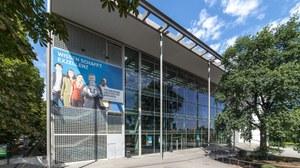 """Frontansicht des Hörsaalzentrums der TU Dresden. Am Gebäude Hängt ein Poster mit der Aufschrift: """"Wissen Schafft Exzellenz""""."""