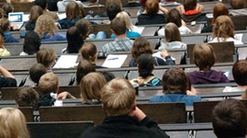 Das Foto zeigt einige Sitzreihen eines Hörsaals voller Studierender aus der Perspektive einer im Saal sitzenden Person. Viele der Studierenden schauen nach vorn oder machen sich Notizen.