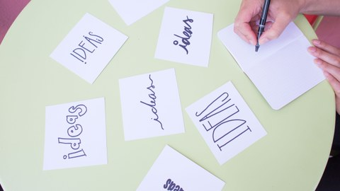 """Tisch mit Notizzetteln, auf denen """"Ideas"""" in verschiedenen Schriftzügen steht"""