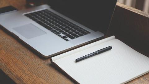 Das Foto zeigt einen Laptop mit schwarzem Bildschirm, rechts daneben ein geöffnetes, leeres Notizbuch und einen daraufliegenden Stift  auf einer hölzernen Oberfläche.