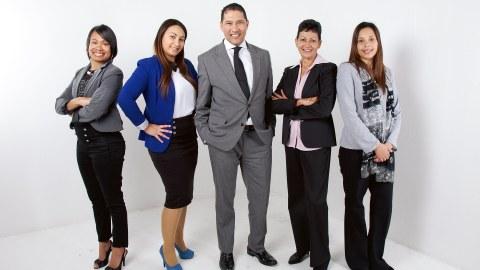 Das Foto zeigt fünf Personen, welche vor einem weißen Hintergrund stehen und lächelnd zur Kamera schauen.