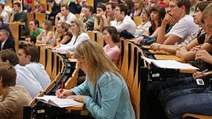 Das Foto zeigt einen Hörsaal voller Studierender während einer Vorlesung. Viele der Studierenden schauen nach vorn oder machen sich Notizen.