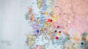 Das Foto zeigt eine Weltkarte, auf welcher der europäische Kontinent in den Fokus gerückt wurde. In einigen der Länder stecken Pinnadeln mit unterschiedlich farbigen Köpfen.