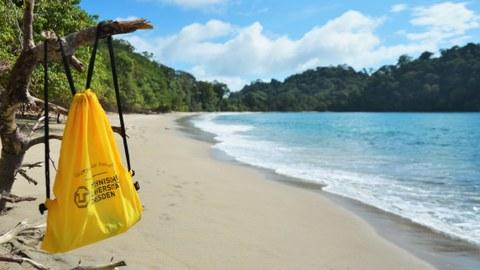 Strand in Ecuador mit gelbem TU-Beutel