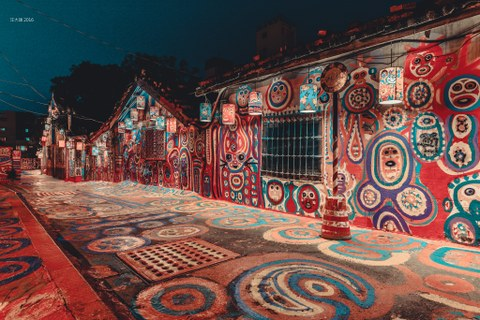 A narrow street with little houses, all colourfully painted.
