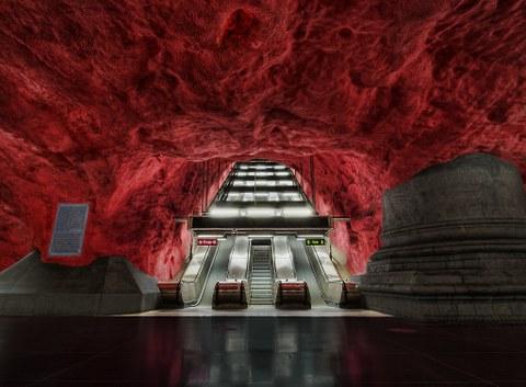 Unter einer leuchtend roten Höhlendecke beginnt eine Rolltreppe