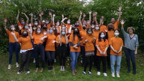 Eine Gruppe von Studierenden stehen zusammen vor einer Baumgruppe. Sie tragen orangefarbene T-Shirts, Mund-Nasen-Bedeckungen und strecken ihre Arme in die Höhe
