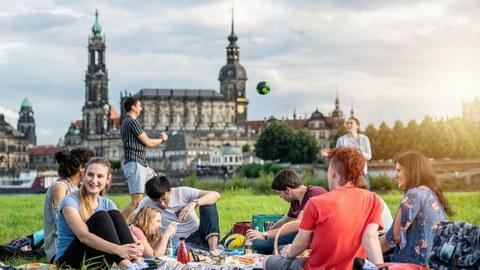 Foto: Gruppe von Studenten an der Elbe. Sie spielen Volleyball und sitzen plaudernd auf der Wiese.