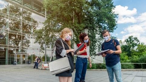 Das Foto zeigt drei Studierende auf dem Platz vor dem Hörsaalzentrum der TU Dresden. Alle drei Personen tragen einen Mund- und Nasenschutz. Sie Halten Notizbücher und Mappen in den Händen und reden miteinander.