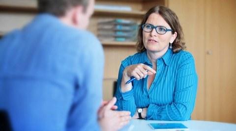 eine Studienberaterin im Gespräch mit einem Studenten
