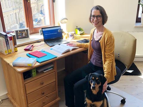 Professorin sitzt zu Hause mit ihrem Hund vor Ihrem Schreibtisch und schaut in die Kamera.