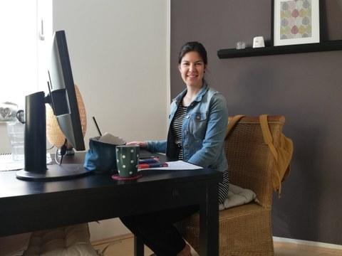 Frau sitzt zu Hause am Schreibtisch vor ihrem Computer und schaut in die Kamera.