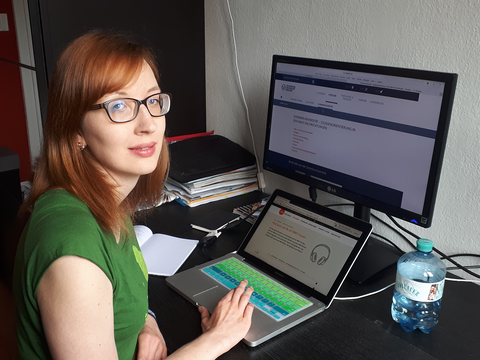 Frau sitzt vor Laptop und Computer am Schreibtisch.