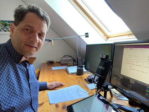 Professor Beitelschmidt sitzt am Schreibtisch zu Hause vor Mikrofon und Computer.