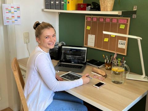 Studentin sitzt zu Hause am Schreibtisch vor ihrem Computer und Tablet.