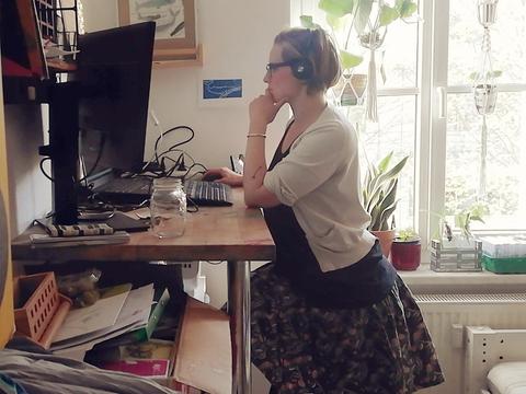 Frau steht vor Ihrem Schreibtisch und schaut auf den Computerbildschirm.