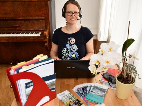 Frau sitzt mit Headset am Schreibtisch vor dem Laptop.