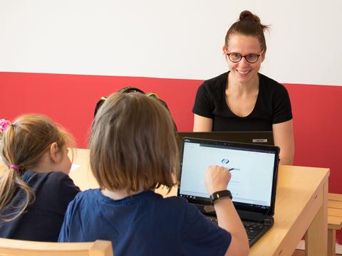 Frau sitzt zwei Kindern am Laptop gegenüber und macht mit ihnen Hausaufgaben.