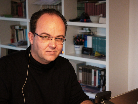 Mann sitzt an Schreibtisch und trägt ein Headset.