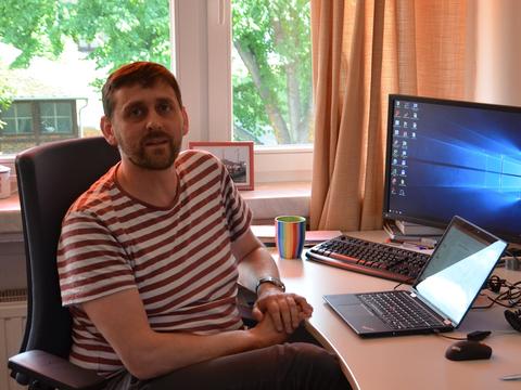 Mann sitzt zu Hause an seinem Schreibtisch vor dem Computer.