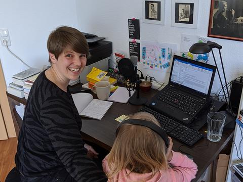 Frau sitzt zu Hause an Schreibtisch und arbeitet, während ihre Tochter neben ihr sitzt.