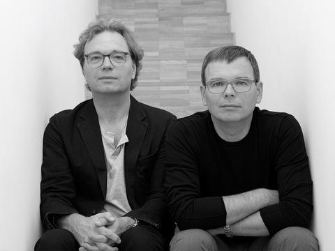 Zwei Männer sitzen auf Treppe und schauen in die Kamera.
