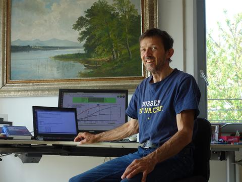 Mann sitzt zu Hause am Schreibtisch vor zwei Bildschirmen.