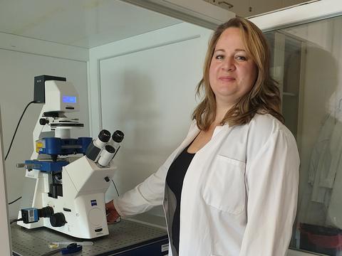 Frau trägt einen Laborkittel und steht vor einem Mikroskop.