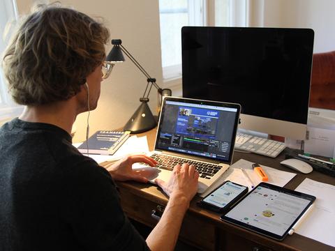 Mann sitzt am Schreibtisch und schreibt am Laptop, neben ihm liegen Handy und Tablet.