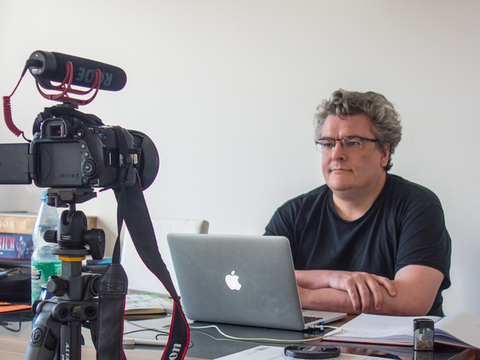 Professor Albers sitzt am Schreibtisch vor Kamera.
