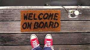 Draufsicht rote Chucks vor einer Fußmatte mit dem Schriftzug Welcome on Board