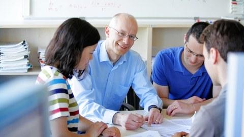 ein Professor im Gespräch mit Studierenden