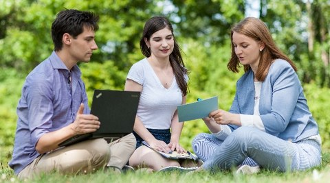 Zu sehen ist ein Foto von drei Studierenden, welche auf einer Wiese sitzen. Links im Bild sitzt ein junger Mann mit einem Laptop auf dem Schoß. In der Mitte und rechts sitzen zwei junge Frauen. Die Frau rechts hält eine Karteikarte in der Hand.
