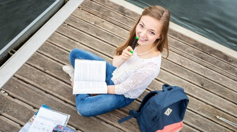 A young woman laughs into the camera. She is sitting on a jetty by the water and holds a pen and a book in her hands.