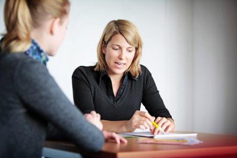 Es ist ein Foto von zwei Personen während eines Gespräches zu sehen. Eine Frau sitzt mit dem Rücken zur Kamera. Die andere Frau – eine Studienberaterin – ist gut von vorn zu erkennen.