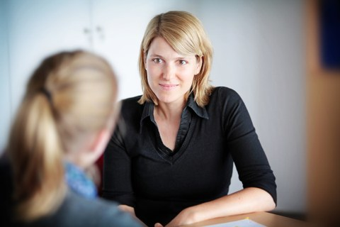 There is a photo of two people during a conversation. One woman is sitting with her back to the camera. The other woman - a student counsellor can be seen well from the front.