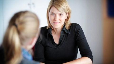 Es ist ein Foto von zwei Personen während eines Gespräches zu sehen. Eine Frau sitzt mit dem Rücken zur Kamera. Die andere Frau – eine Studienberaterin ist gut von vorn zu erkennen.