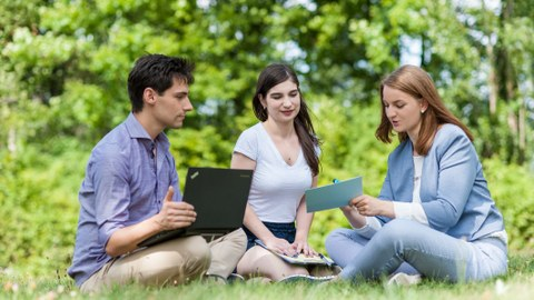 You can see a photo of three students sitting on a meadow. On the left of the picture sits a young man with a laptop on his lap. In the middle and on the right sit two young women. The woman on the right is holding an index card in her hand.