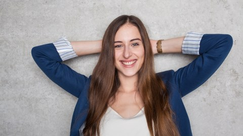 The image shows a photo of a young woman in front of a bright wall. She folds her hands behind her head and smiles at the camera.