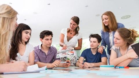 Auf diesem Foto sind mehrere Personen während eines Workshops zu sehen. Fünf Studierende sitzen an einem großen Tisch, auf welchem unterschiedliche Büroutensilien liegen. Zwei Frauen stehen am Tisch und wenden sich den Studierenden zu.