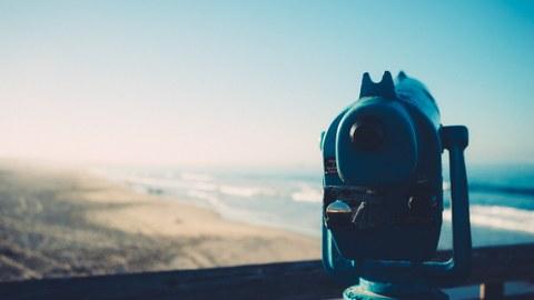 Fernrohr mit Blick auf weite Landschaft mit blauem Himmel