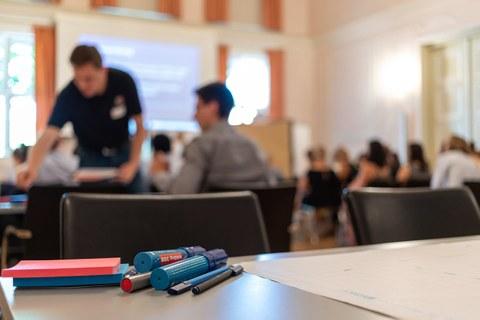 Blick über einen Workshoptisch in den Saal