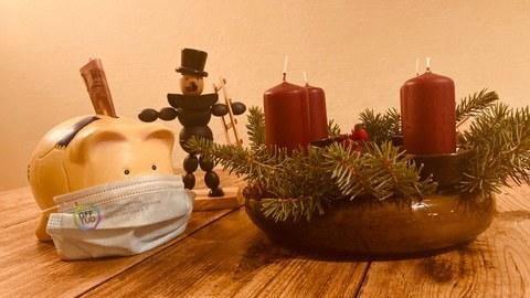 Sparschwein mit Maske in weihnachtlichem Setting