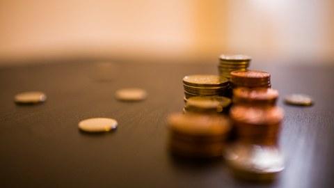 Das Foto zeigt mehrere Stapel an Münzgeld auf einem Tisch. Weiterhin liegen vereinzelte Geldstücke auf dem Tisch.