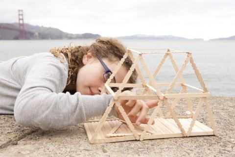Foto von Mädchen, dass vor Meereskulisse an einem Holzmodell baut