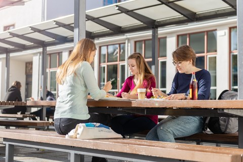 Drei junge Frauen sitzen beim Essen an einem Tisch im Außenbereich der Mensa.