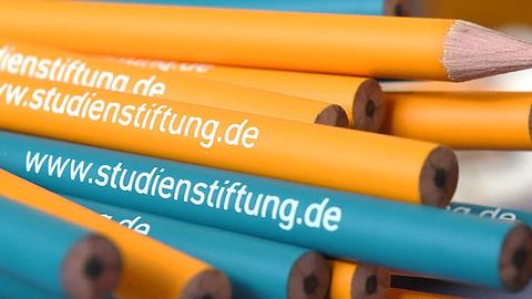Bleistifte in orange und blau mit dem weißen Schriftzug www.studienstiftung.de