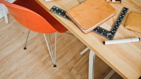 Schreibtisch mit Stuhl und Schreibutensilien